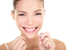 holistic dental patient flossing teeth